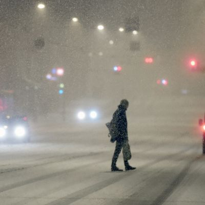 Mies kävelee kadulla lumisateessa.