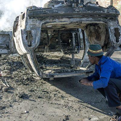 Asukkaat katsovat palavaa autoa Jeppestownin kaupunginosassa Johannesburgissa.