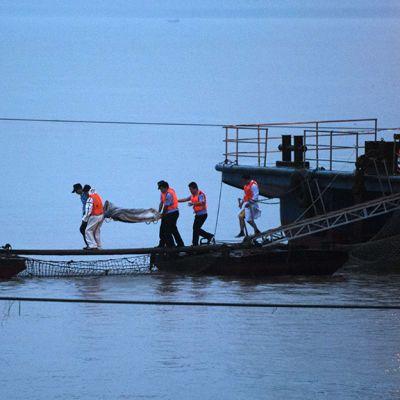 Pelastustyöntekijät kantavat ruumispussia lautalta.