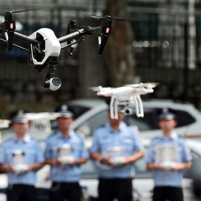 Lukuisia radio-ohjattavia koptereita ilmassa ja poliiseja takana ohjaamassa niitä.
