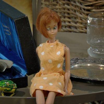 Pop-antiikkia pöydällä. Edessä pikku sammakko ja Barbie-nukke, takana hopealusikoita.