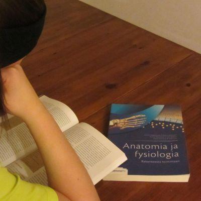 Tyttö lukee pääsykoekirjaa.