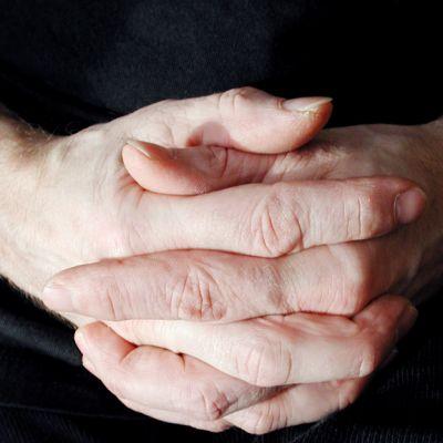 Miehen rukoilevat kädet.