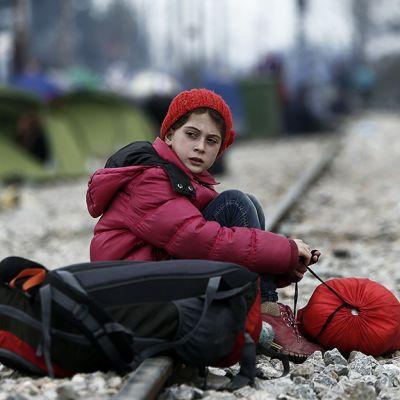 Pakolaislapsi istumassa rautiekiskoilla