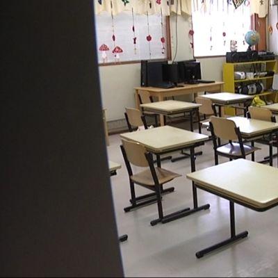 Tyhjä luokkahuone, jossa muutamia pulpetteja.