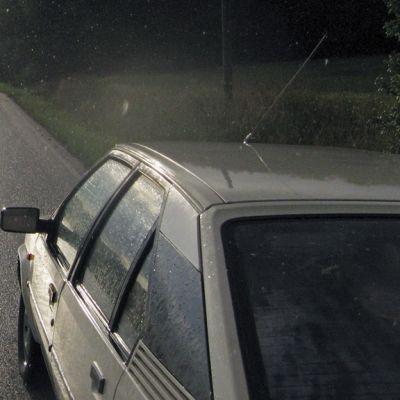 Auto kesäsateessa maantiellä.