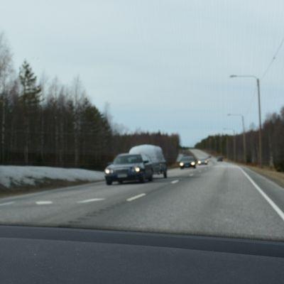 Näkymä auton tuulilasista: neljän auton letka vastaan tulevien kaistalla.