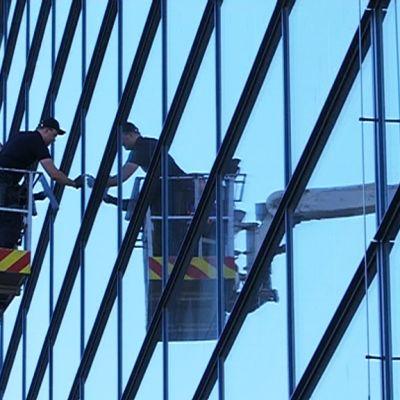 Kolme miestä pesee Sibeliustalon ikkunoita nostokorista.