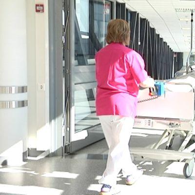 Sairaanhoitaja kuljettaa potilasta sängyllä.