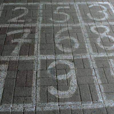 Asvalttiin piirrettyjä lasten pihapeliin liittyviä numeroita.