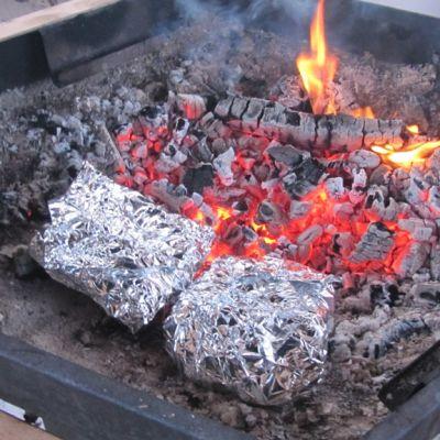 Ruokaa paistumassa folioiden sisällä hiilloksen päällä.
