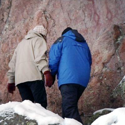 Jukka Parkkinen ja Tuija Wetterstrand tutkivat kalliomaalausta Juusjärvellä.