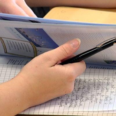 Opiskelija selaa ruotsin oppikirjaa.