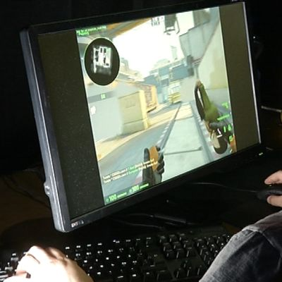 Mies pelaa tietokoneella Counter-Strike -peliä