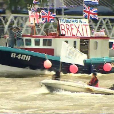 """Veneitä joella. Kuvan keskellä olevassa aluksessa on kyltti, jossa lukee """"The only way is... BREXIT"""". Edustalla ajaa pienempi moottorivene, jossa on myös lippu. Kuva on epäselvä, mutta lipussa lukee """"IN"""". Taustalla on kolmas alus. Joen vesi on harmaankellervää."""