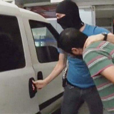 Naamioitunut mies siirtää käsiraudoitettua miestä auton kyytiin.