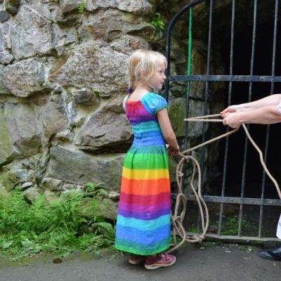Pieni tyttö katsoo, kun nainen yrittää avata rautaporttia köydellä.