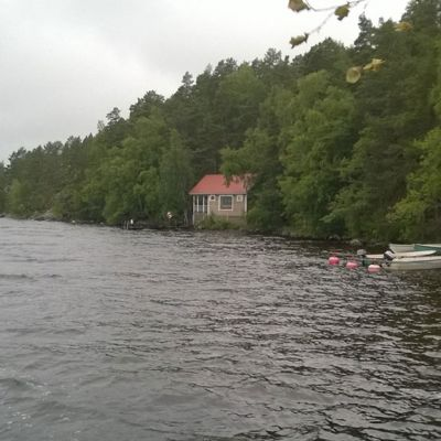 Rantaa, metsää, veneitä  taustalla  punakattoinen ruskehtava rakennus.