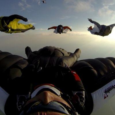 Laskuvarjohyppääjät lentävät liitopuvuissa