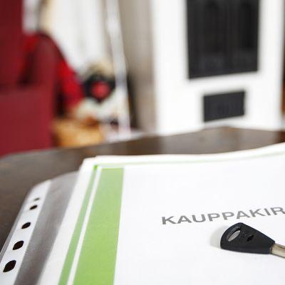Kauppakirja ja avain pöydällä.