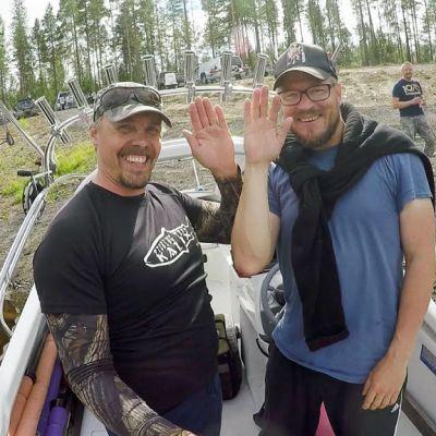 Kaksi miestä vilkuttaa veneestä.