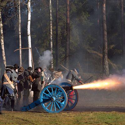 1700-luvun tykillä ammutaan, ympärillä sotilaspuvussa olevat miehet pitävät käsiä korvien suojana