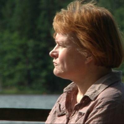 Nainen istuu laiturilla ja katselee järvelle.