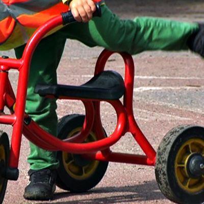 Lapsi ajaa kolmipyörällä tarhassa.