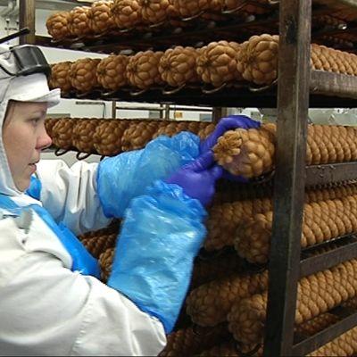 Kuvassa nainen leikkaa makkaraa tehtaassa