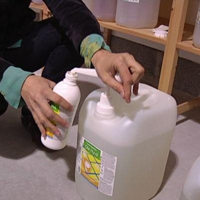 Kädet pumppaavat pesuainetta täyttöpulloon