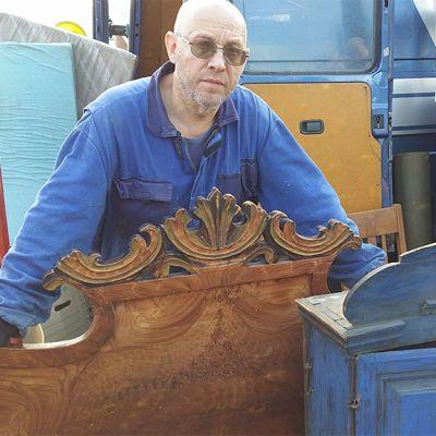 Antiikkikauppias Raul Pohjonen. Kuvassa näkyy myös vanhoja huonekaluja, kaappeja ja muuta tavaraa.