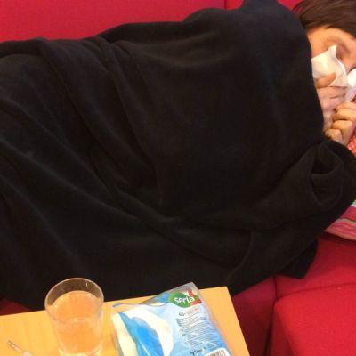Nainen makaa punaisella sohvalla mustan peiton alla ja niistää.