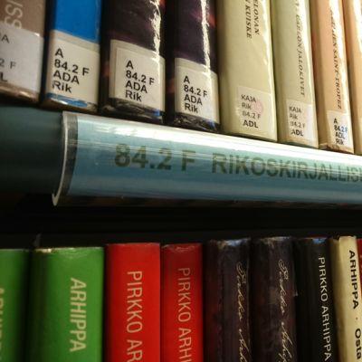 Rikosromaaneja kirjaston hyllyssä.