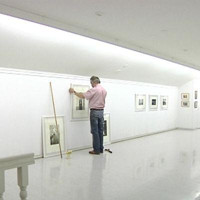 Esa Riippa ripustaa töitään taiteilijakoti Taide-Vionojan näyttelytilaan Ullavassa.