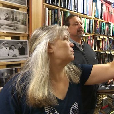Antikvariaatin myyjä esittelee kirjoja.