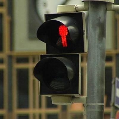 Liikennevalo jalankulkijoille palaa punaisena