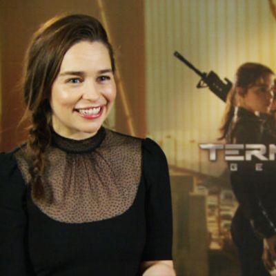 Hymyilevä näyttelijä Emilia Clarke Terminator Genisys -elokuvajulisteen edellä.