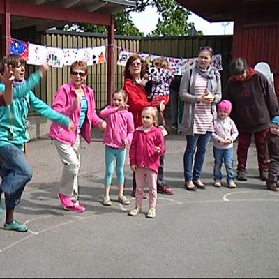 Aikuiset ja lapset leikkivät leikkipuistossa.