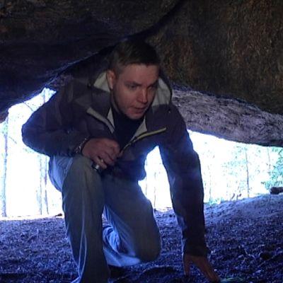 Mies kömpii luolaan.