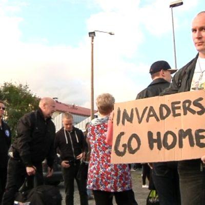 """Mielenosoitus Forssassa, miehellä kyltti """"Invaders go home"""""""