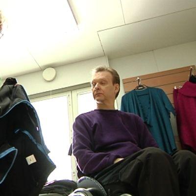 Pyörätuolissa istuva Mika katselee takkia.