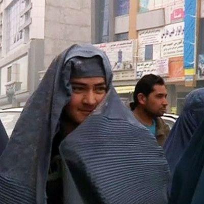 Miehiä burkhiin pukeutuneina.