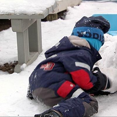 Lapsia lumileikeissä päiväkodin pihalla.