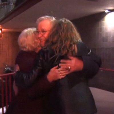 Mies ja kaksi naista halaavat.