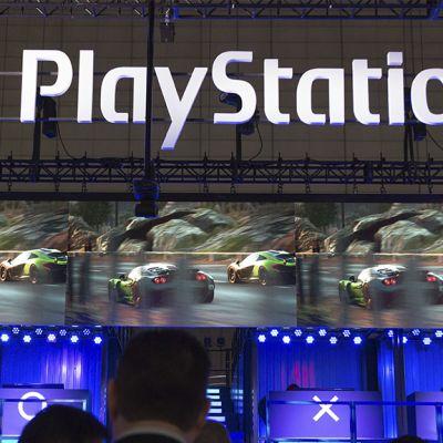 Playstation-kyltti ja näyttöjä joissa on kuvaa autopelistä.
