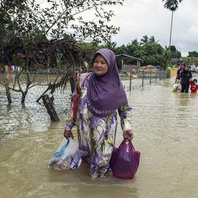 Nainen kävelee tulvavedessä.