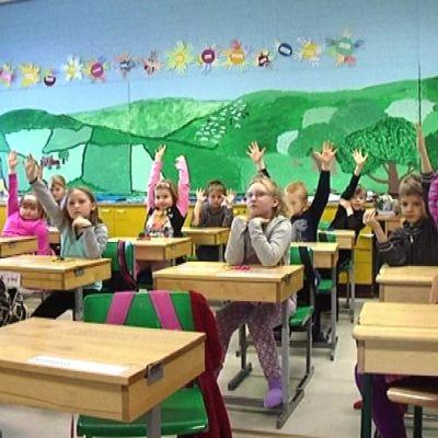 Koululaisia luokassa viittaamassa