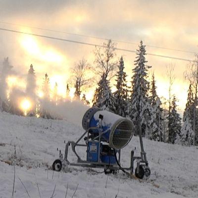 Lumitykki puhaltaa lunta rinteeseen Häkärinteillä.