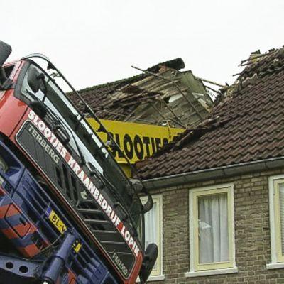 Kuvassa kallellaan oleva kuorma-auto, jonka lavalla oleva nosturi on kaatunut kaksikerroksisen, pitkän rivitalon päälle.