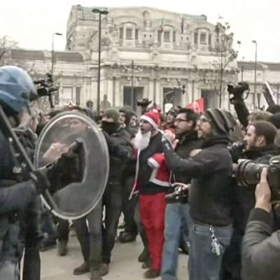 mellakkapoliiseja ja mielenosoittajia, joiden joukossa joulupukki